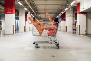 Woman in shopping cart in the middle of an empty warehouse
